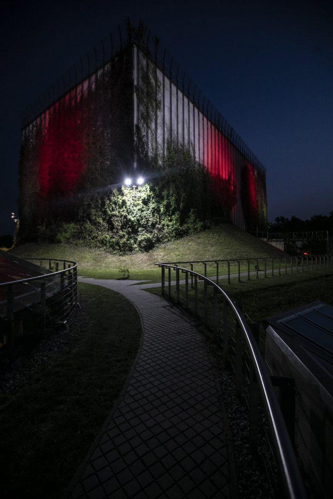 Zielone tarasy i część budynku Opery wieczorem. Budynek podświetlony na biało-czerwono.
