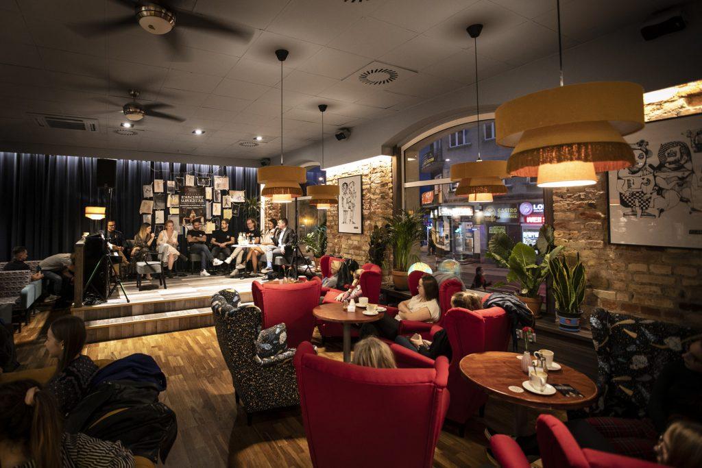 Sala kawiarniana. Przy stolikach , na czerwonych fotelach siedzi kilka osób. Dalej, przed czarną kotarą siedzą wykonawcy musicalu ''Jesus Christ Superstar''.