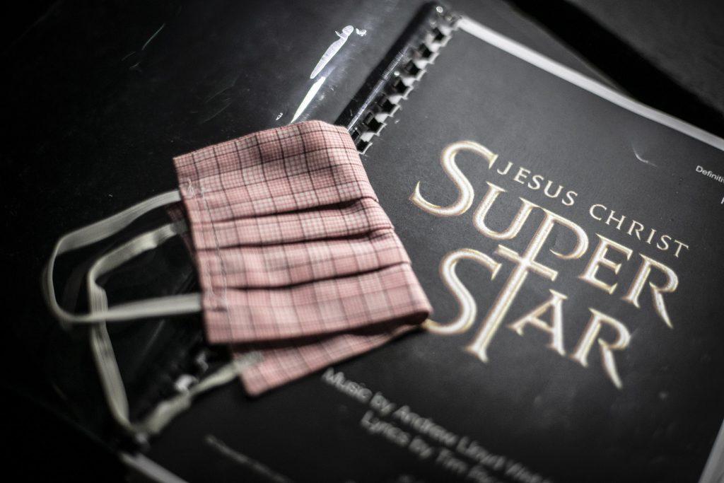 Na czarnym skoroszycie z napisem ''Jesus Christ Superstar'' leży maseczka ochronna.