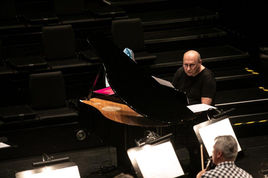 Sala kameralna. Na zdjęciu dwóch mężczyzn. Jeden siedzi przy pianinie, drugi siedzi obok przy pulpicie do nut.