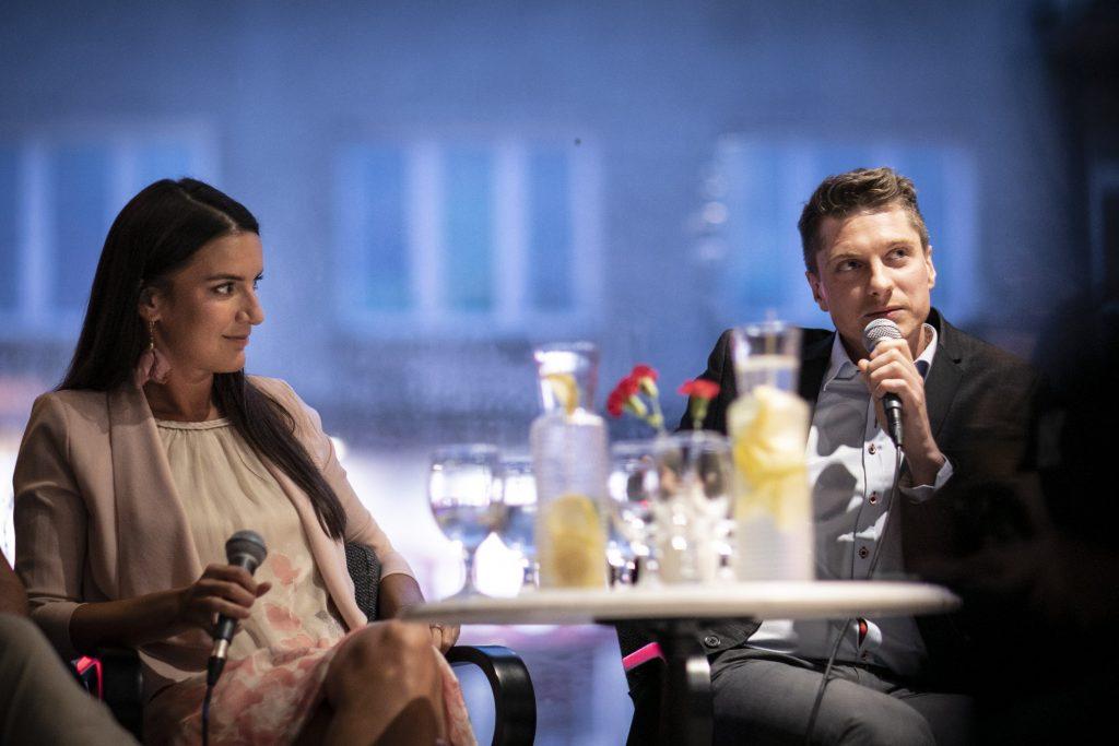 Dwójka wykonawców musicalu ''Jesus Christ Superstar'' siedzi przy stoliku. Mężczyzna mówi trzymając mikrofon, kobieta siedząca obok patrzy na niego.