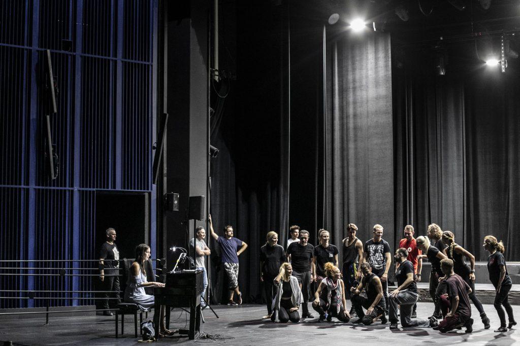 Na scenie grupa kobiet i mężczyzn. Kilkanaście osób stoi, przed nimi kilka osób klęczy na jednym kolanie. Rozmawiają ze sobą. Po lewej stronie, przy pianinie siedzi kobieta.