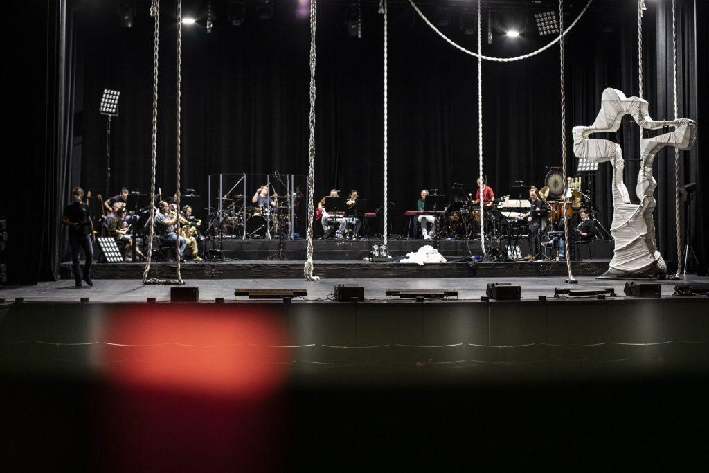 Widok na scenę. Po lewej stronie stoi duży, metalowy krzyż owinięty białym materiałem. Z góry zwisają białe liny. Dalej siedzi orkiestra.
