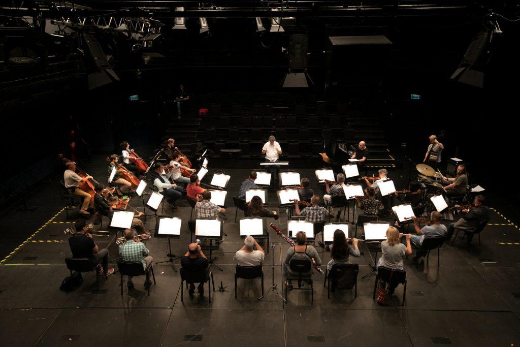 Widok z góry na scenę sali kameralnej. Przed pulpitami na których leżą rozłożone nuty, siedzi orkiestra. Przed nimi siedzi dyrygent. Próba do koncertu.