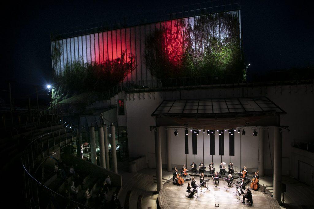 Widok z góry na budynek Opery i amfiteatr podczas koncertu wieczornego. Na scenie orkiestra kameralna. Po lewej stronie widownia w ciemności. Budynek Opery podświetlony na biało-czerwono.