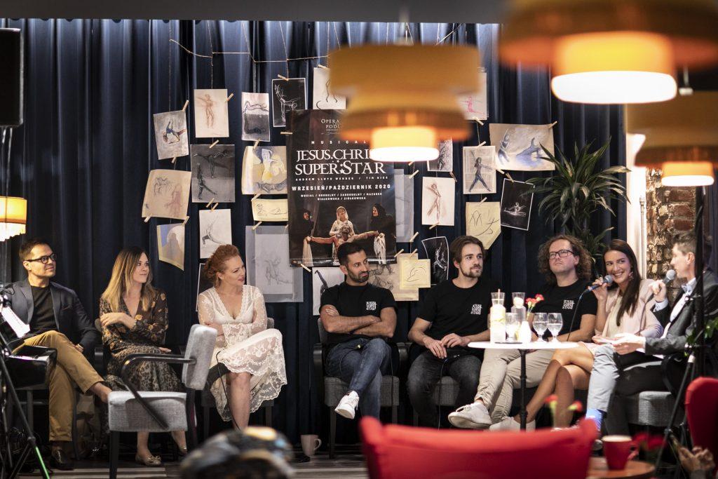 Wykonawcy musicalu ''Jesus Christ Superstar'' siedzą przed kotarą z rysunkami i plakatem promującym musical. Dwoje z nich trzyma mikrofony rozmawiając. Reszta patrzy w ich kierunku.