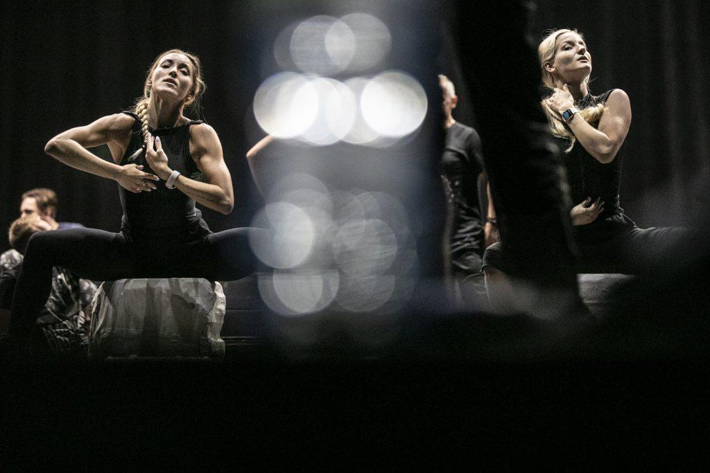 Dwie kobiety na dużych , białych kamieniach siedzi w pozycji tanecznej. Dalej za nimi stoi kilku mężczyzn.