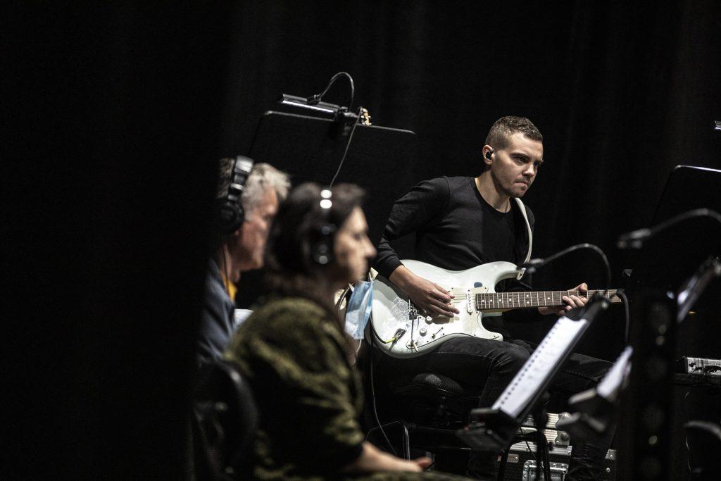 Trzech mężczyzn siedzi przy instrumentach. Jeden z nich gra na gitarze elektrycznej. Dwóch na uszach ma słuchawki.