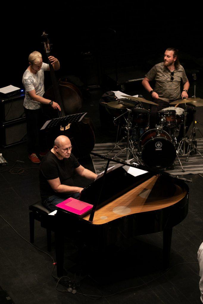 Trzech muzyków przy instrumentach: perkusji, kontrabasie i pianinie, podczas próby do koncertu.