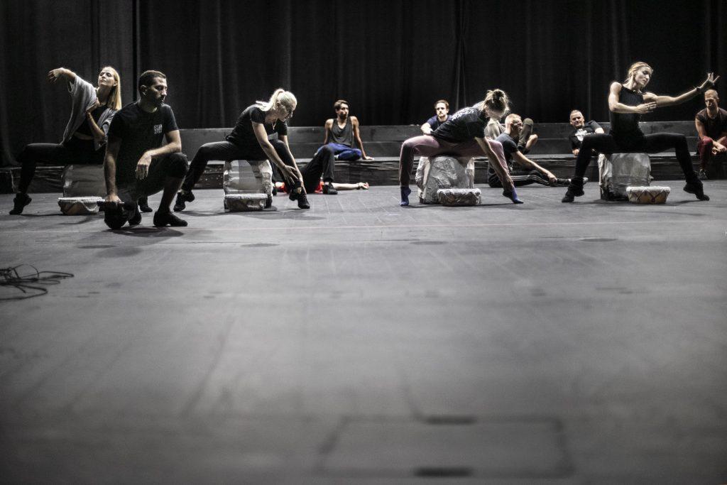 Na scenie, z przodu kilka kobiet siedzi na białych, dużych kamieniach w pozycji tanecznej. Dalej, na podeście scenicznym siedzi kilku mężczyzn. Po lewej stronie klęczy na jednym kolanie mężczyzna.