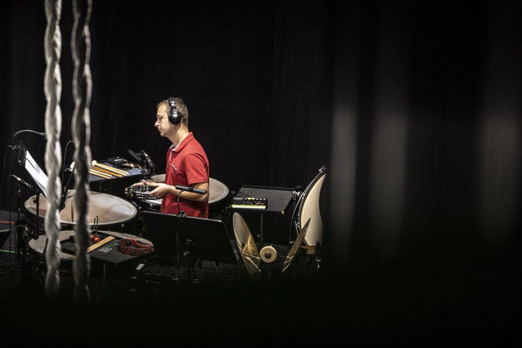 Mężczyzna w czerwonej koszulce stoi przy zestawie perkusyjnym. Na uszach ma słuchawki. W ręku trzyma