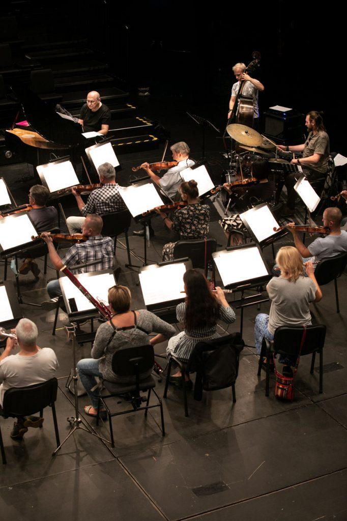 Kilkunastu muzyków orkiestry podczas próby do koncertu na sali kameralnej.