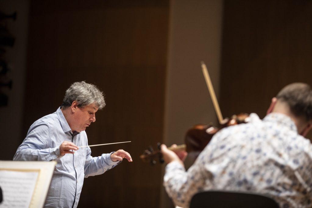 Po lewej stronie dyrygent Prof. Mirosław Jacek Błaszczyk trzyma ręce w geście dyrygowania, po prawej mężczyzna siedzący tyłem gra na skrzypcach.