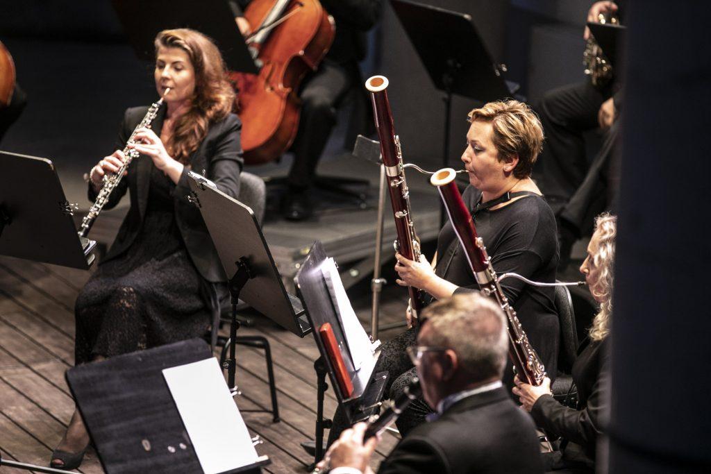 Kliku muzyków podczas koncertu. Po prawej stronie dwie kobiety grające na fagotach, po lewej stronie kobieta grająca na oboju. Obok nich mężczyzna grający na klarnecie.