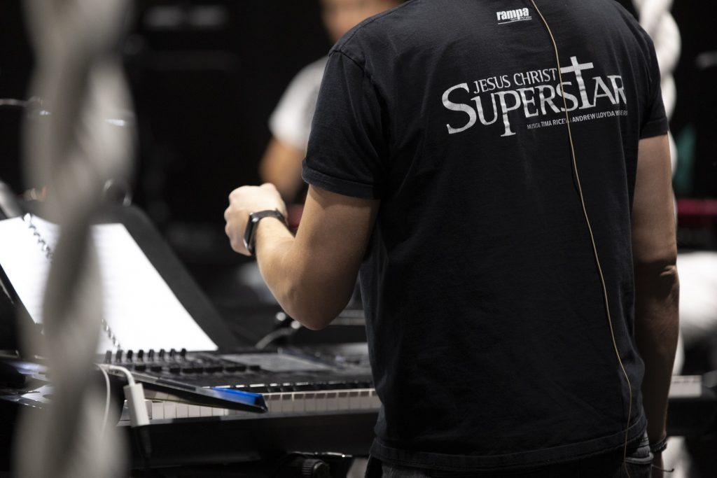 Mężczyzna stoi tyłem. Na czarnej koszulce ma napis ''Jesus Christ Superstar''. Przed nim stoi elektryczne pianino.