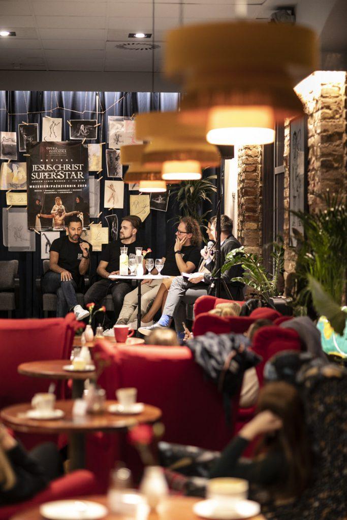 Wykonawcy musicalu ''Jesus Christ Superstar'' siedzą przy stoliku wzdłuż kotary na której wiszą rysunki oraz plakat promujący musical. Jeden z mężczyzn mówi przez mikrofon. Wszyscy patrzą w jego stronę. Z przodu kawiarniane stoliki , wokół nich czerwone fotele.