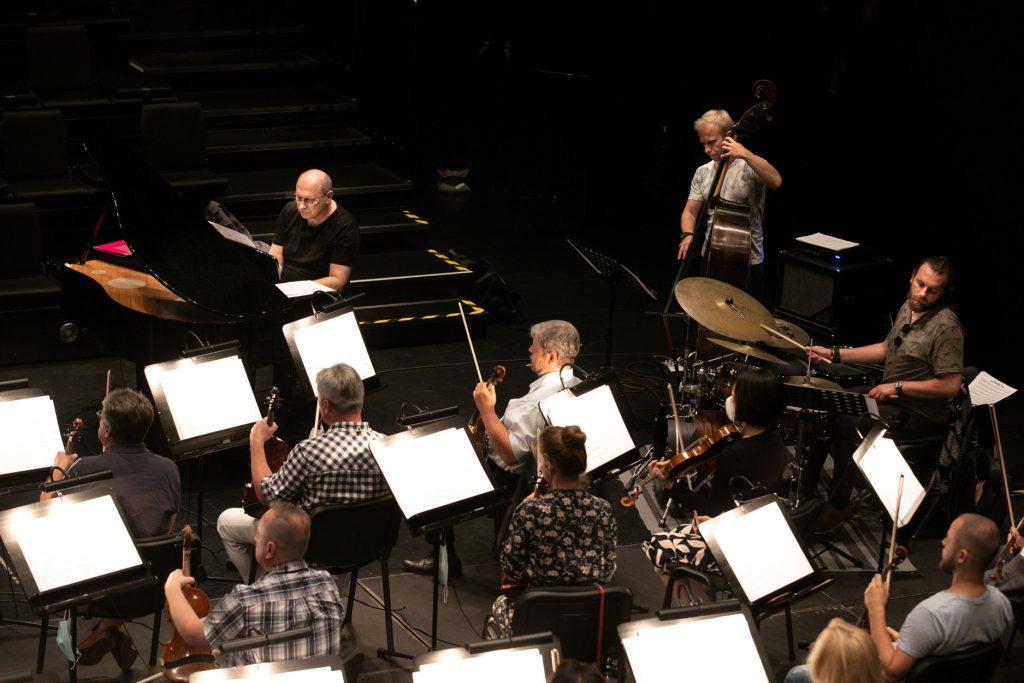 Próba do koncertu. Tyłem, przy pulpitach na których leżą rozłożone nuty siedzi kilku artystów orkiestry.