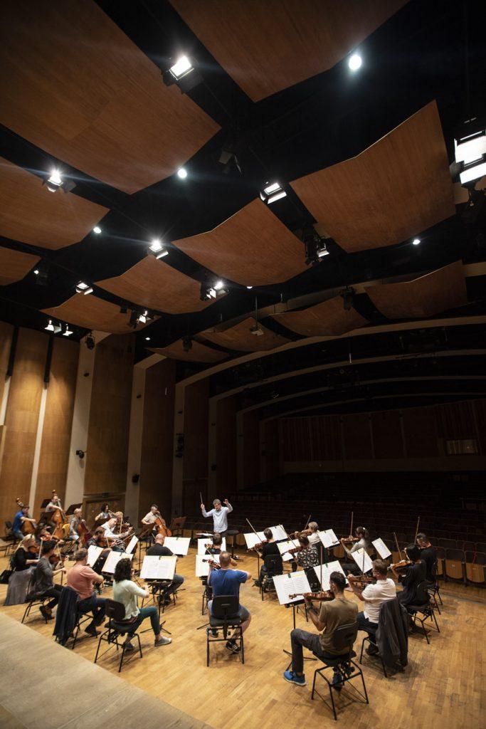 Próba do koncertu. Na scenie gra orkiestra kameralna Opery i Filharmonii Podlaskiej. Przed nimi stoi dyrygent.