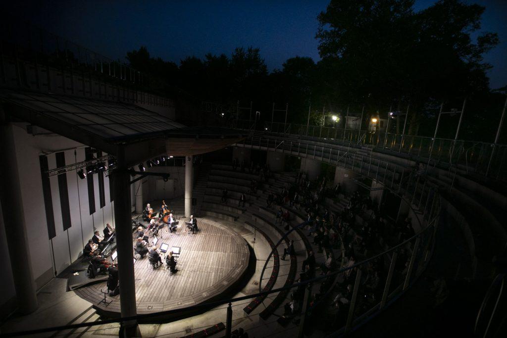 Zdjęcie zrobione z góry. Po lewej stronie podświetlona scena amfiteatru na której gra orkiestra kameralna. Po prawej stronie publiczność w półmroku.