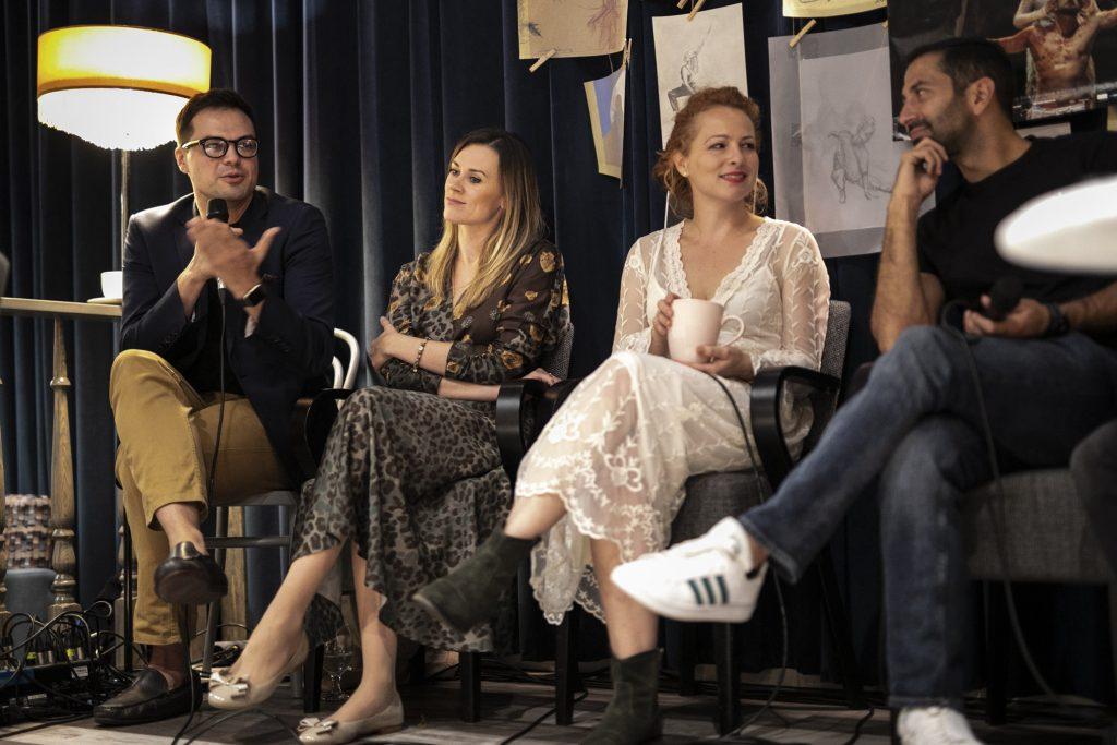 Wykonawcy musicalu ''Jesus Christ Superstar'' , dwie kobiety i dwóch mężczyzn, siedzą przed kotarą na której wiszą rysunki oraz plakat promujący musical.