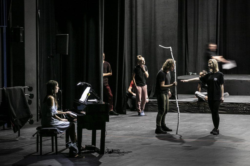 Po lewej stronie siedzi kobieta przy pianinie. Dalej stoi mężczyzna , trzyma w ręku długą gałąź opierając się na niej. Przed nim stoi kobieta z wyciągniętą ręką do przodu. Kilka osób siedzi na podestach scenicznych.