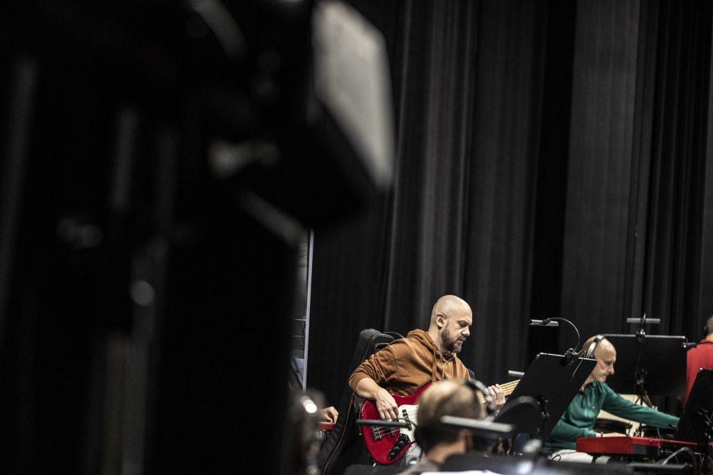 Dwóch mężczyzn siedzi przy pulpitach do nut. Jeden gra na elektrycznym pianinie, drugi gra na elektrycznej gitarze.