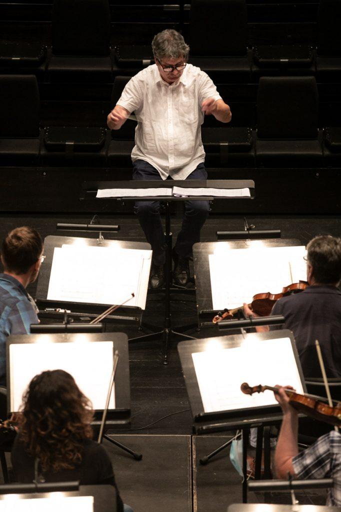 Na zdjęciu widać cztery pulpity na których leżą nuty. Obok nich siedzi grupa skrzypiec. Przed nimi siedzi dyrygent.