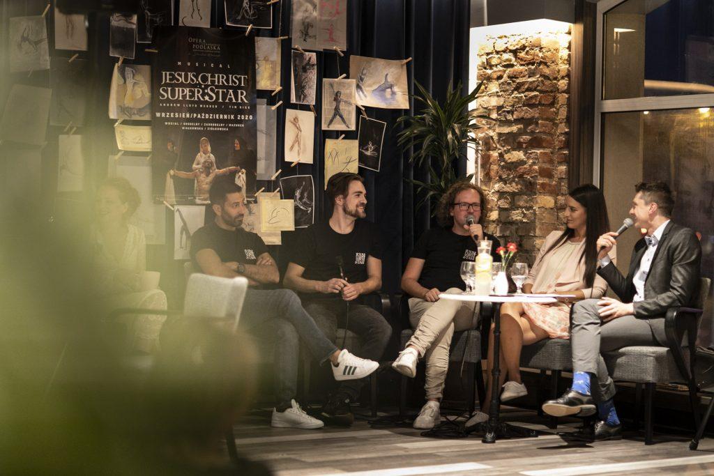 Wykonawcy musicalu ''Jesus Christ Superstar'' siedzą przy stoliku wzdłuż kotary na której wiszą rysunki oraz plakat promujący musical. Jeden z mężczyzn mówi przez mikrofon. Wszyscy patrzą w jego stronę.