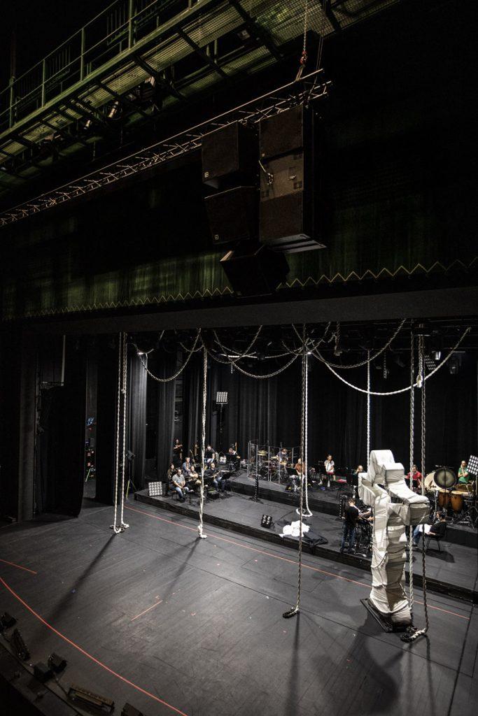 Widok z boku na scenę. Po prawej stronie duży metalowy krzyż owinięty białym materiałem. Z góry zwisają białe liny o różnym splocie. W rogu sceny, przy pulpitach siedzą muzycy.