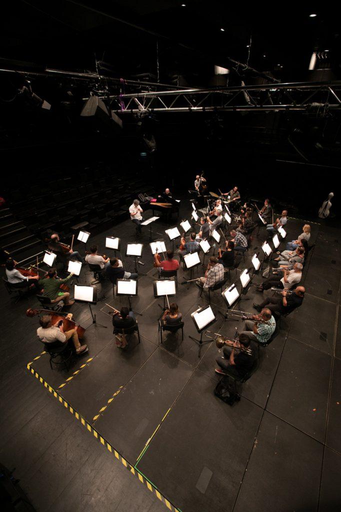 Próba na sali kameralnej. Zdjęcie zrobione z góry. Przed pulpitami na których leżą rozłożone nuty, siedzi orkiestra. Przed nimi siedzi dyrygent.