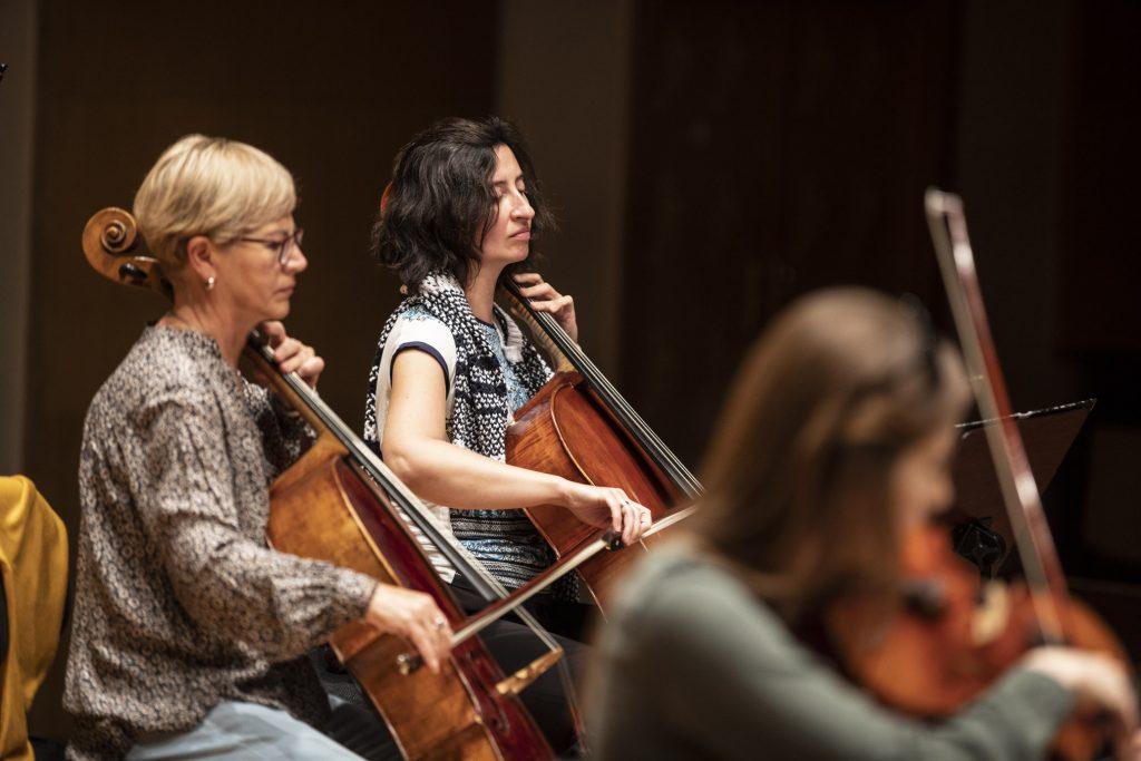 Trzy kobiety grające na instrumentach. Dwie wiolonczelistki, jedna altowiolistka.