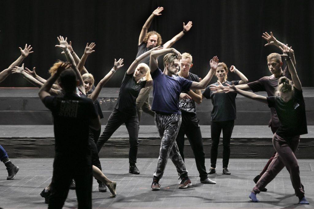 Grupa osób , kobiet i mężczyzn tańczy z rękoma uniesionymi do góry. Przed nimi mężczyzna , trzyma rękę do góry w geście tłumaczenia.