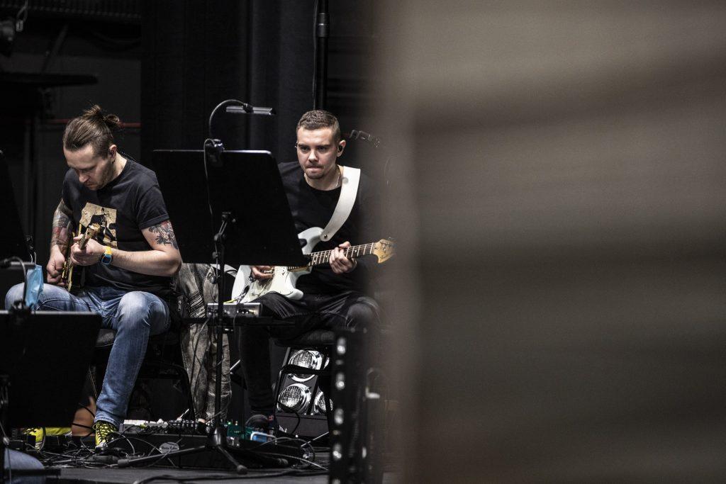 Dwóch mężczyzn siedzi przy pulpitach grając na gitarach elektrycznych.