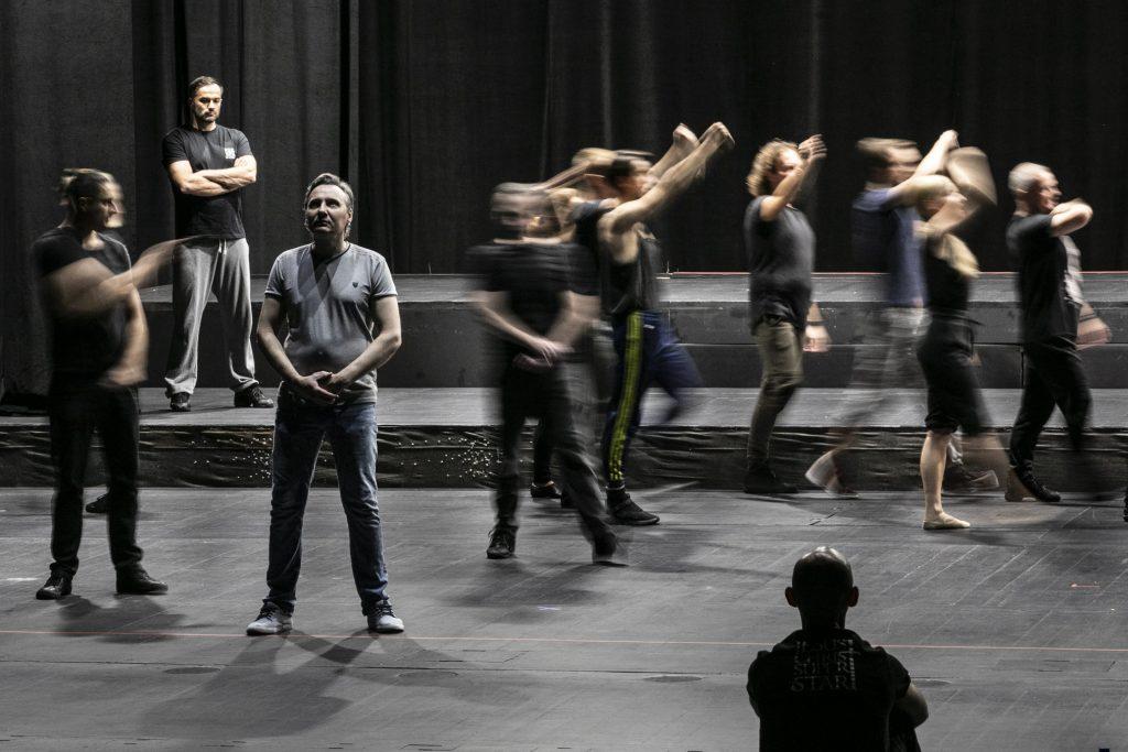Na scenie kilka osób. Część z nich tańczy trzymając ręce uniesione do góry. Kilku z nich stoi w bezruchu.