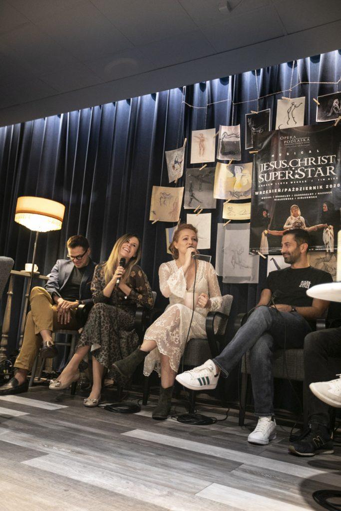 Wykonawcy musicalu ''Jesus Christ Superstar'' , dwie kobiety i dwóch mężczyzn, siedzą przed kotarą na której wiszą rysunki oraz plakat promujący musical. Kobiety trzymają mikrofony , śpiewając.