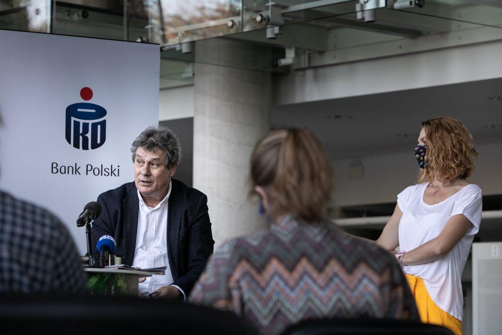 Konferencja prasowa. Na zdjęciu dyrygent Prof. Mirosław Jacek Błaszczyk. Za nim roll up z logo Banku Polskiego PKO.