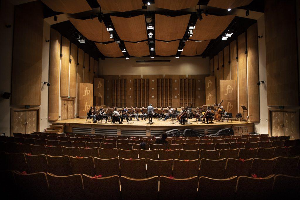 Próba do koncertu. Widok z końca sali, na widowni siedzi mężczyzna. Na scenie orkiestra kameralna wraz z dyrygentem podczas próby.