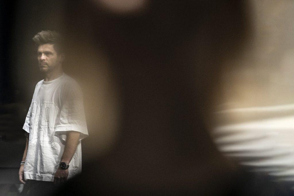 Po lewej stronie mężczyzna w białej koszulce stoi patrząc przed siebie. Na środku kadru ciemna , rozmazana plama.