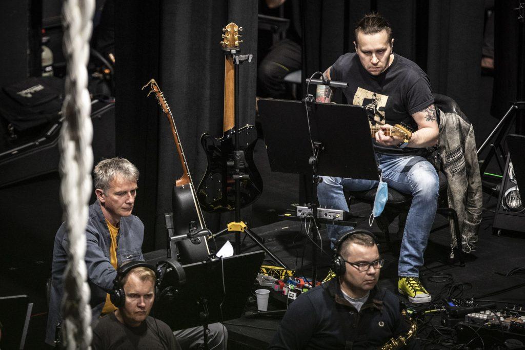 Czterech mężczyzn siedzi przy pulpitach do nut. Dwóch z nich ma słuchawki na uszach. Jeden gra na gitarze.