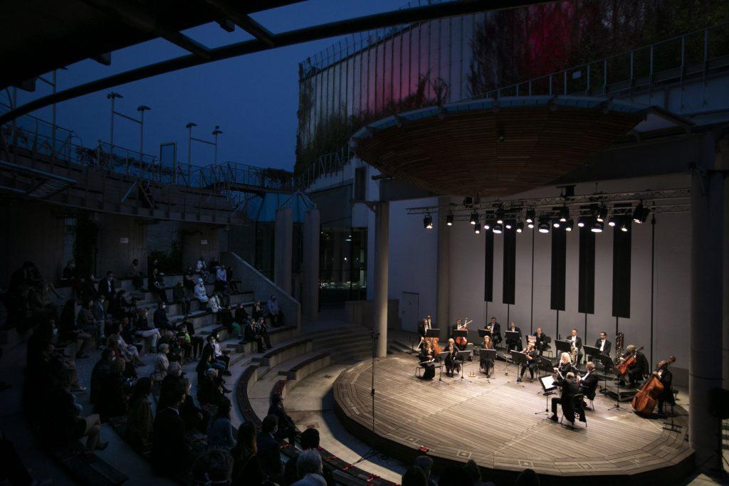 Koncert wieczorny w amfiteatrze. Na scenie orkiestra kameralna Opery i Filharmonii Podlaskiej. Zdjęcie zrobione z boku. Po lewej stronie widownia w półmroku.