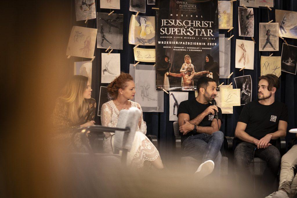 Wykonawcy musicalu ''Jesus Christ Superstar'' , dwie kobiety i dwóch mężczyzn, siedzą przed kotarą na której wiszą rysunki oraz plakat promujący musical. Jeden z mężczyzn mówi przez mikrofon. Wszystkie osoby zwrócone są w jego kierunku.