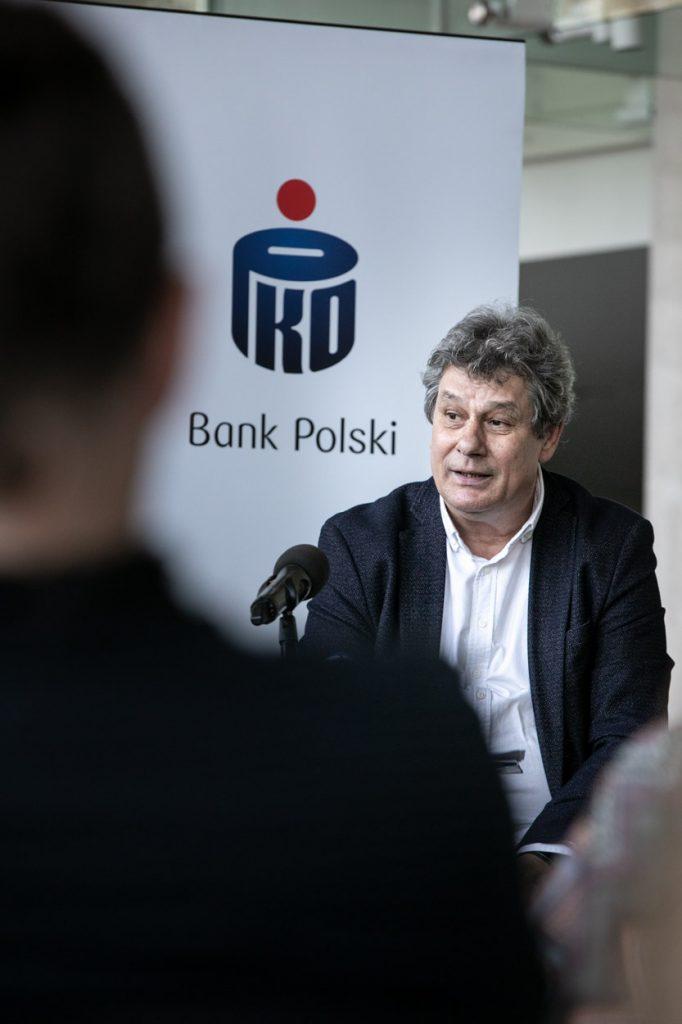 Na zdjęciu Prof. Mirosław Jacek Błaszczyk na konferencji prasowej. Za nim roll up z logo Banku Polskiego PKO.