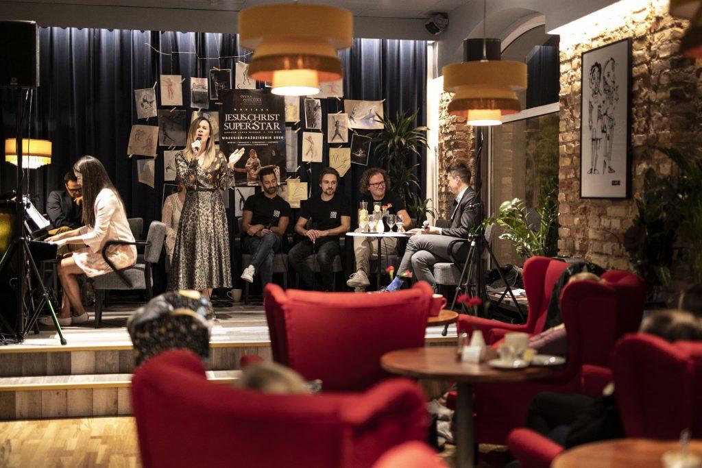 Wykonawcy musicalu ''Jesus Christ Superstar'', dwie kobiety i kilku mężczyzn. Jedna z nich śpiewa stojąc z mikrofonem, druga gra, siedząc przy pianinie. Za nimi kotara, na niej przyczepione rysunki, na środku duży plakat promujący musical ''Jesus Christ Superstar.'' Z przodu stolik kawiarniany i kilka czerwonych foteli.