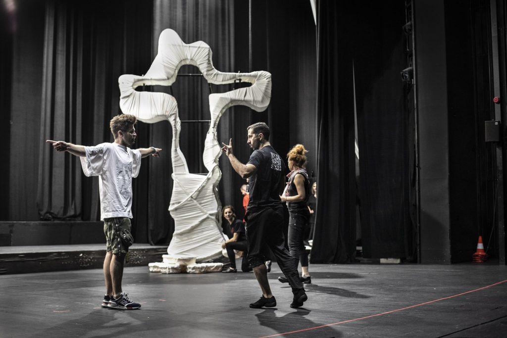 Na scenie stoi duży, metalowy krzyż, owinięty białym materiałem. Przy nim dwóch mężczyzn, jeden z rękoma rozłożonymi na boki, patrzy na mężczyznę który trzyma rękę w geście tłumaczenia. Dalej kilka kobiet stoi.