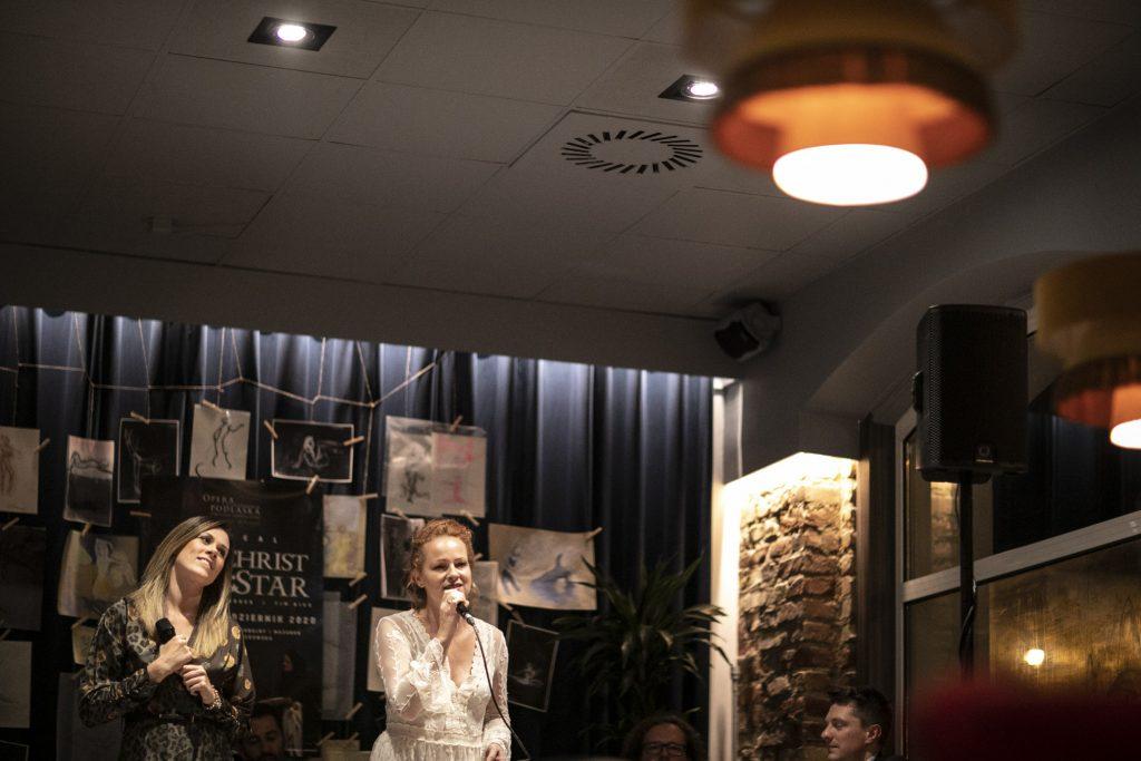 Dwie kobiety z mikrofonami stoją na tle czarnej kotary na której wisi między innymi plakat promujący musical ''Jesus Christ Superstar''.