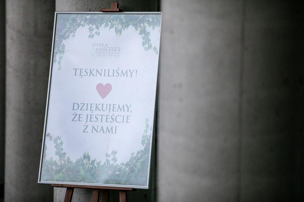 Pomiędzy betonowymi filarami stoi sztaluga. W niej plakat z napisem: ''Tęskniliśmy. Dziękujemy, że jesteście z nami.''