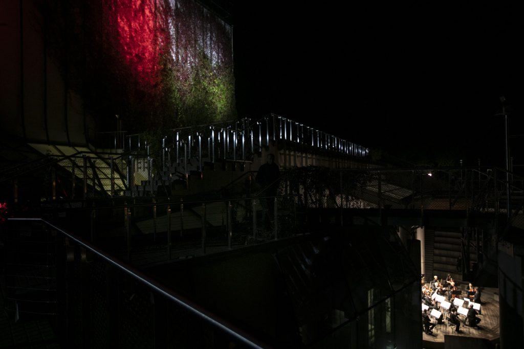 Widok na budynek Opery i Filharmonii Podlaskiej. Po lewej stronie tarasy i część budynku podświetlona na czerwono. Po prawej , widok z góry na scenę letnią, na której odbywa się koncert orkiestry kameralnej.