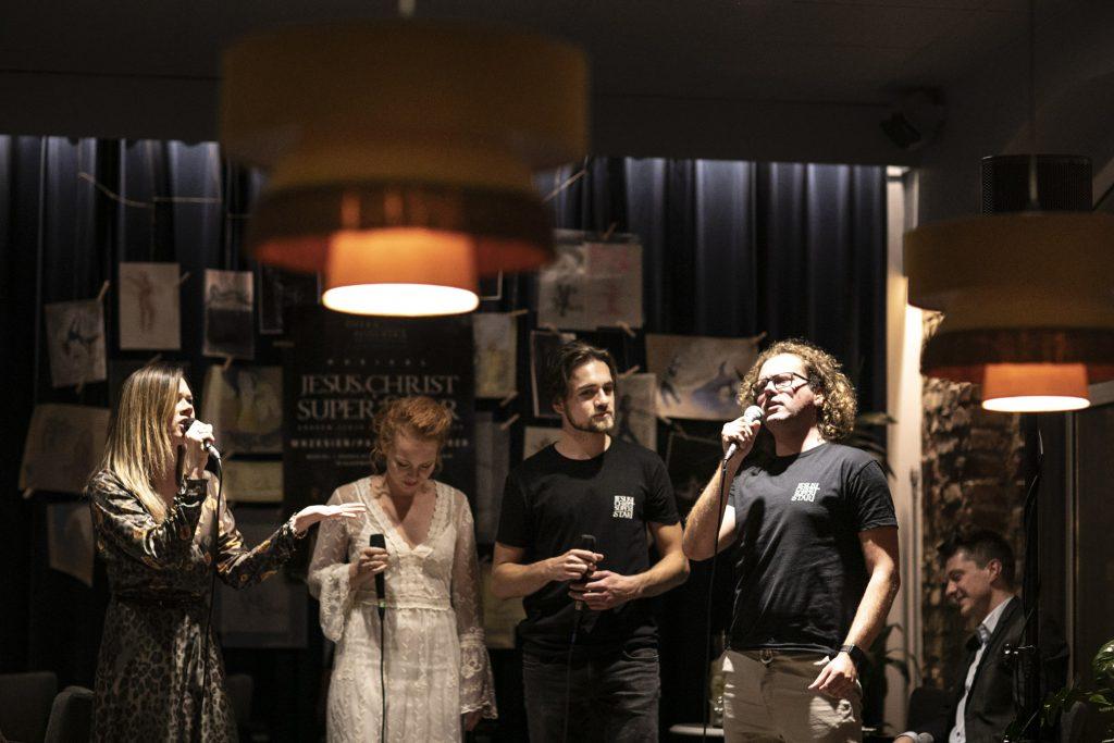 Wykonawcy musicalu ''Jesus Christ Superstar'', dwie kobiety i dwóch mężczyzn stoi obok siebie z mikrofonami. Dwoje z nich śpiewa. Za nimi kotara, na niej przyczepione rysunki, na środku duży plakat promujący musical ''Jesus Christ Superstar.''