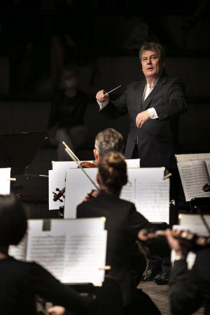 Kilka osób grających na skrzypcach siedzi tyłem. Przed nimi stoi dyrygent Prof. Mirosław Jacek Błaszczyk.