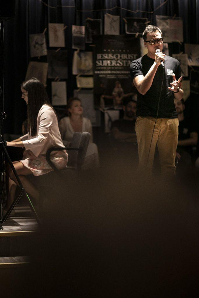 Kilku artystów grających w musicalu ''Jesus Christ Superstar''. Na środku stoi mężczyzna, śpiewa do mikrofonu, obok, tyłem do niego siedzi kobieta. Za nimi na kotarze rysunki oraz plakat promujący musical ''Jesus Christ Superstar''